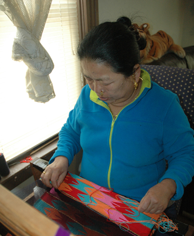 Jahar Ghalley at her loom, Bhutanese Nepali weaving, 2015; Jahar Ghalley; Worcester, Massachusetts; Photography by Maggie Holtzberg