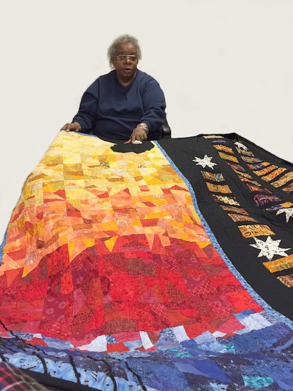 Naomi Henry holding her Jazz Divas quilt, African American quilting guild, 2005; Sisters in Stitches: Joined by the Cloth; Grove Hall, Massachusetts; Cotton and synthetic fabric; 45 x 60 inches; Photography by Maggie Holtzberg