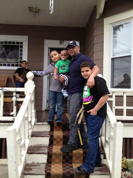Mirabal family on the front steps of their home; Carnival comparsa; 2013: Lawrence, Massachusetts