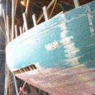 Harold A. Burnham using adze; Wooden boatbuilding & restoration; 200: Essex, Massachusetts
