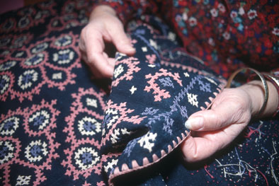 Anahid Kazazian holding Marash embroidery done by her grandmother, circa 1866; Armenian embroidery; 2002: Lexington, Massachusetts