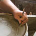 Stephen Earp doing sgraffito on a plate at the treadle wheel; Redware pottery; 2009: Shelburne Falls, Massachusetts; Clay
