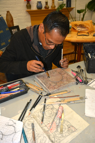 Panit Mai brushing away loose clay. Note his ambidexterity.; Cambodian ornaments; 2016: Lowell, Massachusetts
